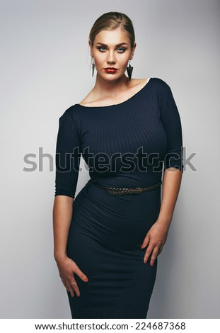 Portrait of attractive young woman posing confidently. Beautiful oversized female model posing proudly against grey background. - stock photo