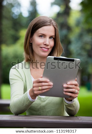Portrait of attractive young woman reading from digital tablet in park