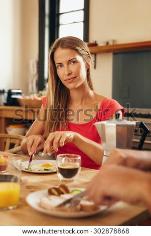 Portrait of attractive young woman sitting at breakfast table eating and looking at camera. Caucasian female having breakfast in kitchen at home. - stock photo