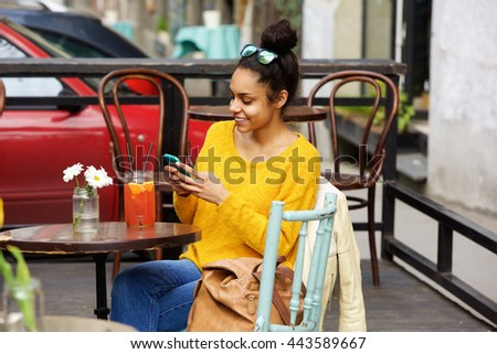 Portrait of attractive young woman sitting at outdoor cafe table and reading text message on her mobile phone