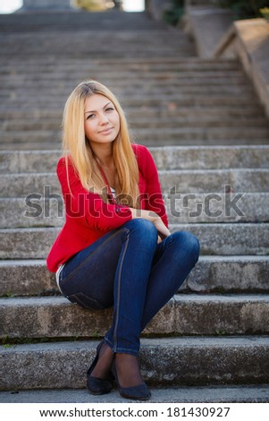 portrait of Attractive young woman sitting on a staircase of an office building