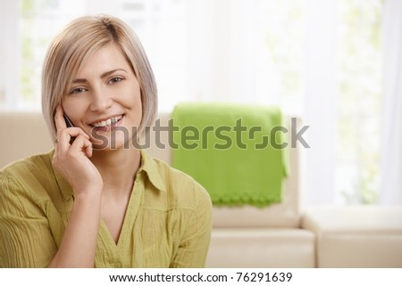 Portrait of attractive young woman speaking on mobile phone at home, smiling at camera.? - stock photo