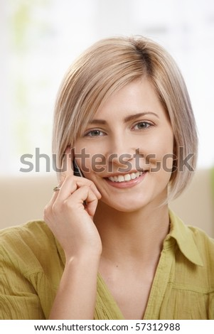 Portrait of attractive young woman speaking on mobile phone at home, smiling at camera. Copyspace on left.? - stock photo