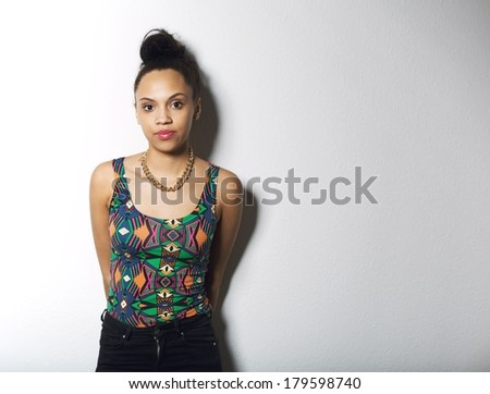 Portrait of attractive young woman standing against grey background with copy space. Beautiful african female model posing in casual clothing. - stock photo