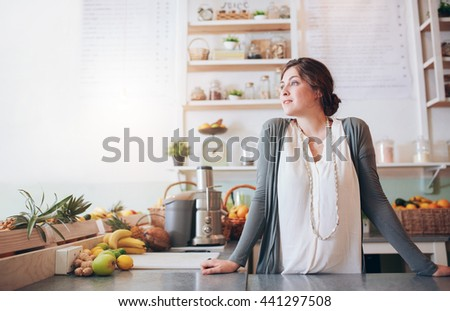 Portrait of attractive young woman standing behind the counter and looking away. Caucasian fruit juice bar owner looking at copy space and thinking. - stock photo
