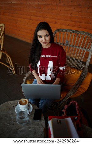 Portrait of attractive young woman using laptop computer sitting in cafe - stock photo