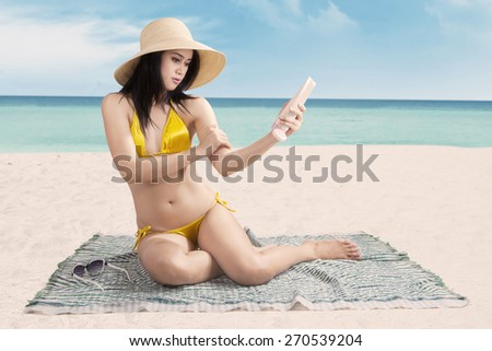 Portrait of attractive young woman wearing bikini at beach and using sunscreen on her skin - stock photo