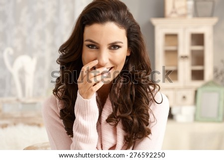 Portrait of attractive young woman with a shy smile. - stock photo