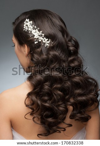 Portrait of attractive young woman with beautiful bridal hairstyle and stylish hair accessory. Brunette with long curly hair, rear view - stock photo