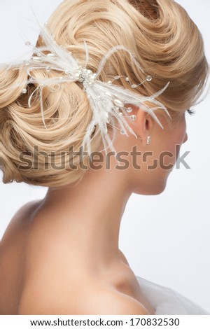 Portrait of attractive young woman with beautiful bridal hairstyle and stylish hair accessory, rear view - stock photo