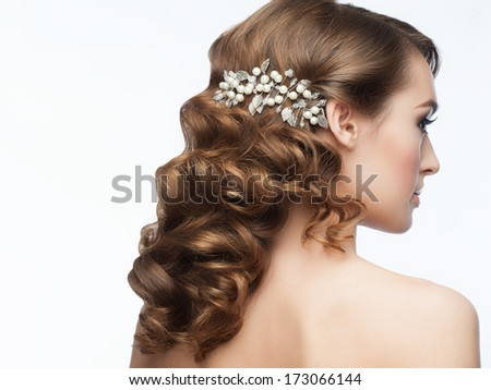 Portrait of attractive young woman with beautiful hairstyle with stylish hair accessory. Girl with long curly hair, rear view - stock photo