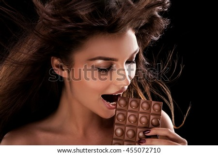 Portrait of attractive young woman with chocolate. Brunette girl . Studio shot.