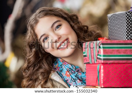Portrait of attractive young woman with Christmas presents in store - stock photo