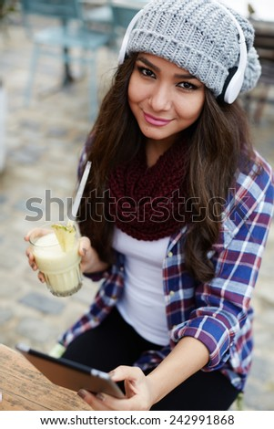 Portrait of attractive young woman with headphones sitting in coffee shop, charming girl holding tropical cocktail looking to the camera - stock photo