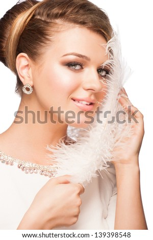Portrait of attractive young woman with makeup and  beautiful hairstyle holding ostrich feather