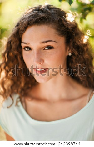 Portrait of Attractive Young Woman with Olive Skin and Curly Hair