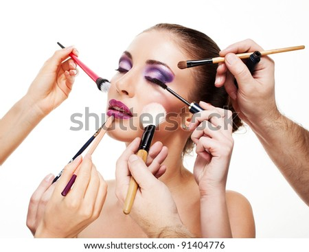 Portrait of attractive young women applying blusher with a lot of brushes on white background - stock photo