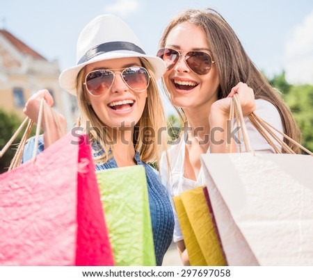 Portrait of attractive young women in sunglasses with shopping bags looking at camera and smiling. - stock photo