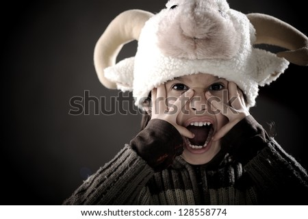 Portrait of authentic cute kid wearing funny sheep hat - stock photo