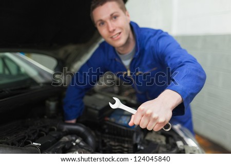 Portrait of auto mechanic with spanner repairing car
