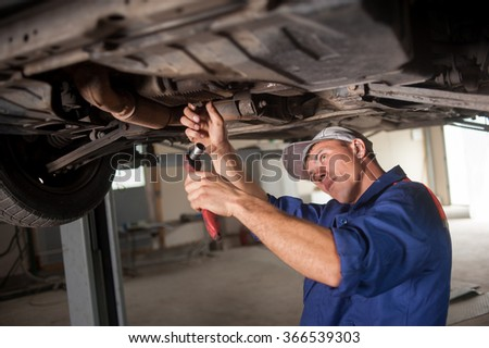 Portrait of auto mechanic working with tools under car in automobile at repair service shop