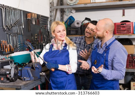 Portrait of auto service center crew with attractive young smiling blonde near tools and equipment