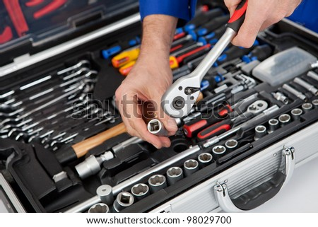 Portrait of automechanic taking a wrench out of toolbox. Isolated on white - stock photo