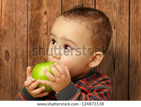 Portrait Of Baby Boy Eating Green Apple against a wooden background - stock photo