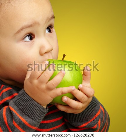 Portrait Of Baby Boy Eating Green Apple against a yellow background - stock photo