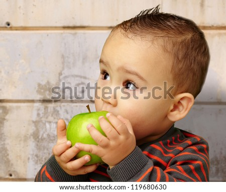Portrait Of Baby Boy Eating Green Apple against an old rusty wall - stock photo
