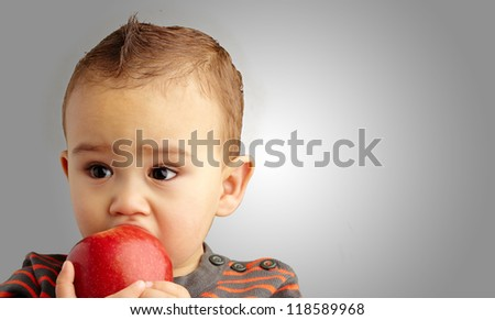 Portrait Of Baby Boy Eating Red Apple against a grey background - stock photo
