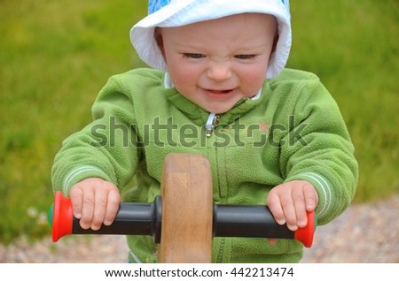 Portrait of  baby boy holding and jumping on a wooden horse in the nature. Child concept.  - stock photo