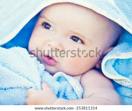 Portrait of baby boy in blue towel - stock photo