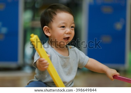 Portrait of baby boy sitting on floor at home - stock photo