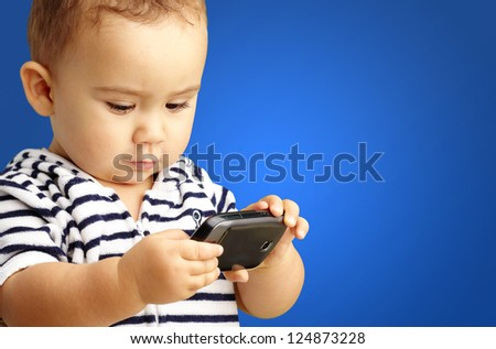Portrait Of Baby Boy Using Cell Phone against a blue background - stock photo