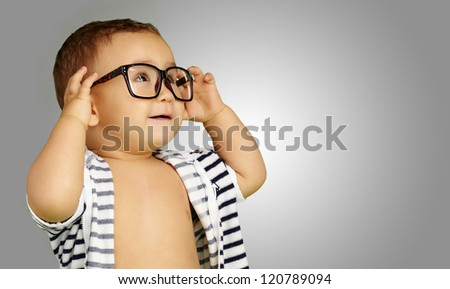 Portrait Of Baby Boy Wearing Eyeglasses against a grey background - stock photo