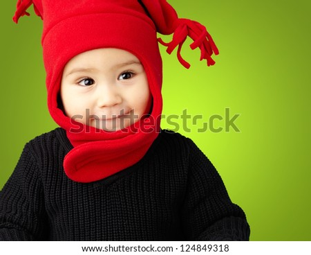 Portrait Of Baby Boy Wearing Warm Clothing against a green background - stock photo