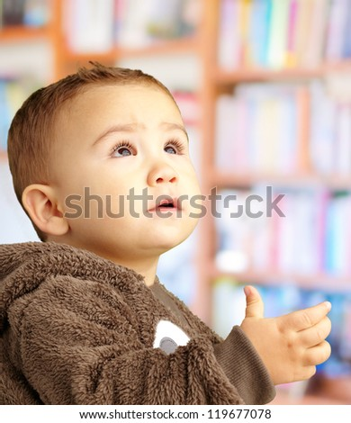 Portrait Of Baby Boy Wearing Warm Clothing at a library - stock photo