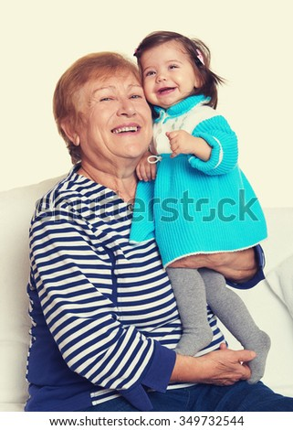 portrait of baby girl and grandmother on white, happy family concept - stock photo