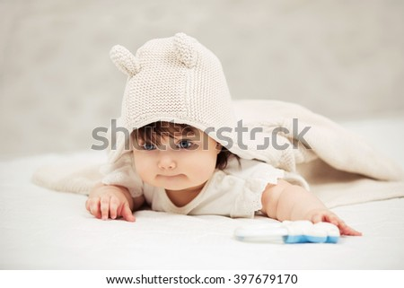 Portrait of baby girl crawling on blanket indoors - stock photo