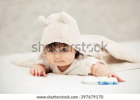 Portrait of baby girl crawling on blanket indoors - stock photo