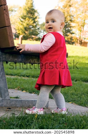 Portrait of baby girl in a pink dress standing near the bench and trying to make her first steps outdoor - stock photo