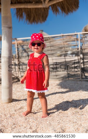 Portrait of baby girl in red dress and hat playing on a beach