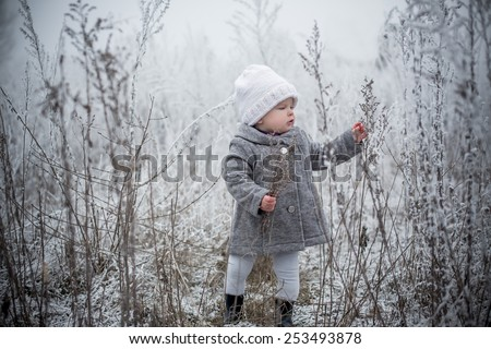 portrait of baby girl in winter covered with snow fairy forest grey and white colors walking alone - stock photo