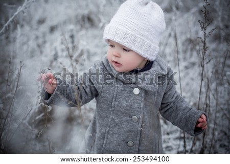portrait of baby girl in winter covered with snow fairy mystery forest grey and white colors walking alone - stock photo