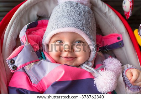 Portrait of baby girl in winter jacket and hat - stock photo