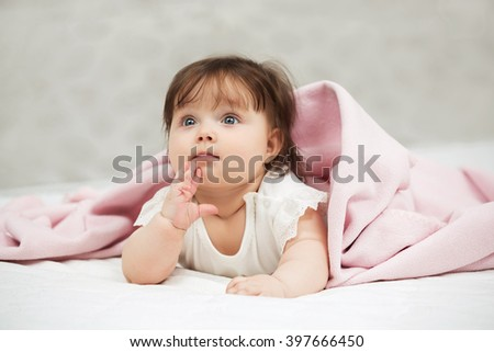 Portrait of baby girl lying on blanket at home - stock photo