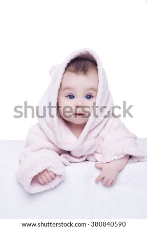 portrait of baby girl on white background. cute little baby girl with big blue eyes in pink bathrobe hood lying on her belly. child is looking into the camera - stock photo