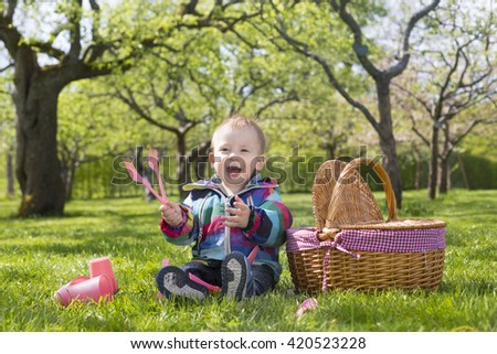 portrait of baby toddler wearing multicolored clothing and gladly sitting with picnic basket on green meadow, playing with plastic flatware - stock photo