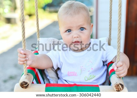 Portrait of baby with backyard swing